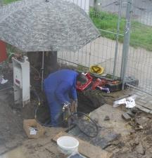 Schweißarbeiten - wegen des Regens unterm Schirm