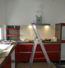 Küchenschränke - mittig hinter der Leiter: Kochfeld und darüber die Abzugshaube
